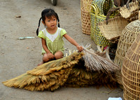 Young girl playing with palm fronds used for thatching, Kompot, Cambodia