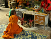 Young monk offering incense, Angkor Wat, Cambodia