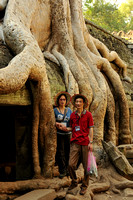 Visitors posing before a strangler fig, Ta Prohm Temple, Siem Reap, Cambodia